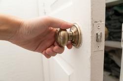 Hand opening the closet door