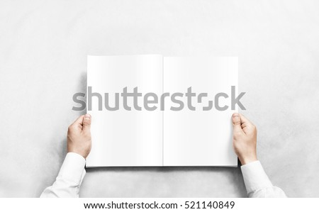 Hand opening white journal with blank pages mockup. Arm in shirt holding clear magazine template mock up.