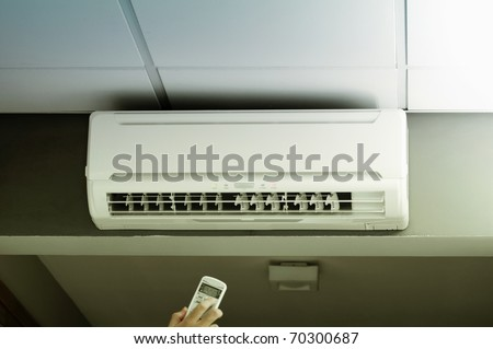 Hand operating remote controller of an air conditioner in modern office.