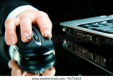 Hand over computer mouse with laptop near by