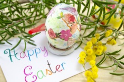 Hand painted decoupage Easter egg on woodensurface with a Happy Easter card