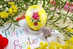Hand painted decoupage Easter egg on woodensurface with a Happy Easter card and two toy rabbit s