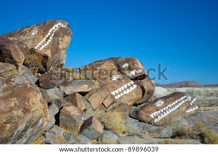 Hand painted monster rock faces near Trona, California in daylight.