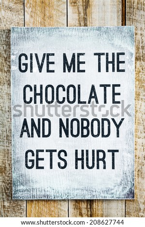 hand-painted motivational wooden vintage board on the rustic wooden background saying Give me the chocolate and nobody gets hurt