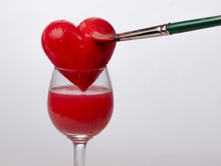 Hand-painted red heart on glass, on a white background