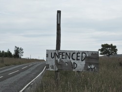 Hand painted sign indicating an un fenced road in Scottish highlands. Peeling paintwork make part of the sign illegible. Large sky and tree frame an uneven road in a bleak landscape.