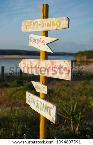 Hand painted wooden direction sign on coastal path directing people towards food, drink, music and danse. #1094807591