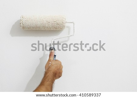 hand painter man at work with a paint roller, wall painting concept #410589337