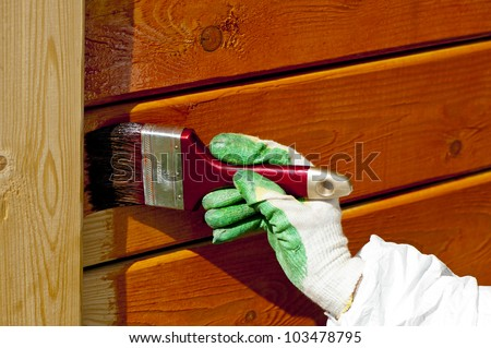 hand painting wooden wall with a paintbrush  in orange outdoor shot