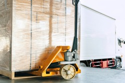 hand pallet truck or pallet jack with cargo shipment on pallet. truck docking load cargo at warehouse. freight industry logistics and transport.