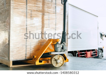 hand pallet truck or pallet jack with shipment product on pallet. truck docking load cargo in warehouse.