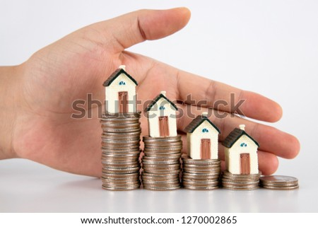 Hand pampered dollar coin and small house model on white background #1270002865