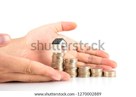 Hand pampered euro coins and small house model on white background #1270002889