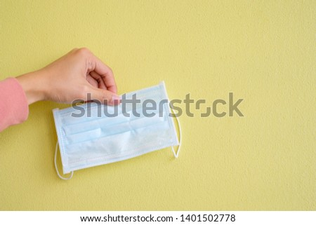 Hand pick up face medical mask protective with copy space on yellow wall texture background for influenza protection or protect from air pollution concept #1401502778