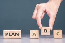 Hand pick up the alphabets wood blocks option in a row, Plan B strategy for business or project concept