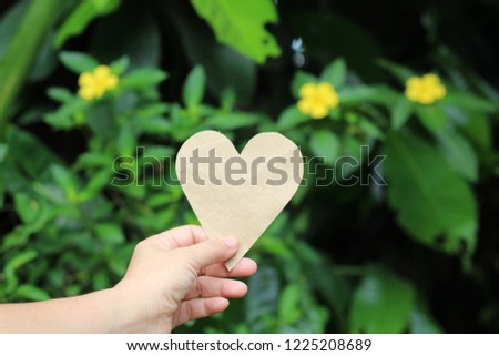 Hand picked paper brown heart. Green background blur #1225208689