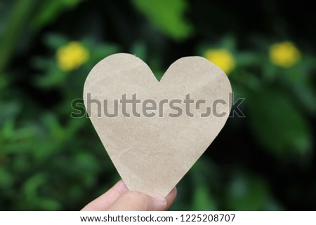Hand picked paper brown heart. Green background blur #1225208707