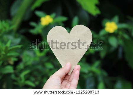 Hand picked paper brown heart. Green background blur #1225208713