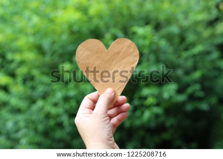 Hand picked paper brown heart. Green background blur #1225208716