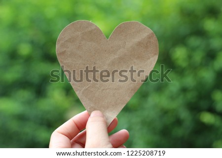 Hand picked paper brown heart. Green background blur #1225208719