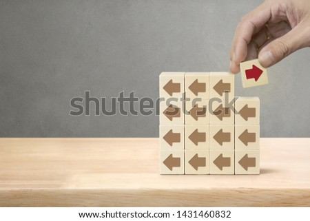Hand picked wooden block with red arrow facing the opposite direction arrows, Unique, think different, individual and standing out from the crowd concept