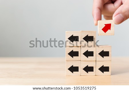 Hand picked wooden block with red arrow facing the opposite direction black arrows, Unique, think different, individual and standing out from the crowd concept