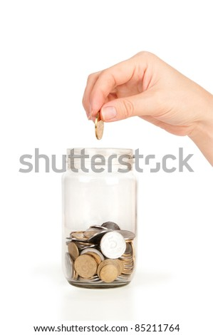 hand picking a coin in glass savings or tips bottle - stock photo