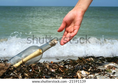 Hand picking a message in a bottle  washed ashore.