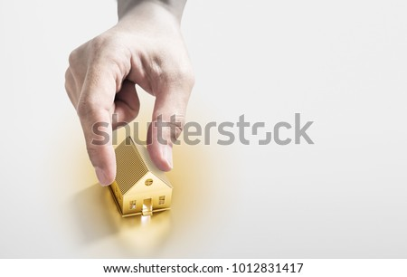 Hand picking golden house, real estate investment and buying house concept #1012831417