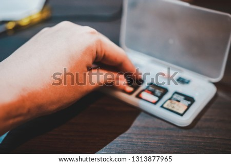 Hand picking SD card in a plastic storage box on the wooden table to be put in portable electronic devices like camera or camcorder #1313877965