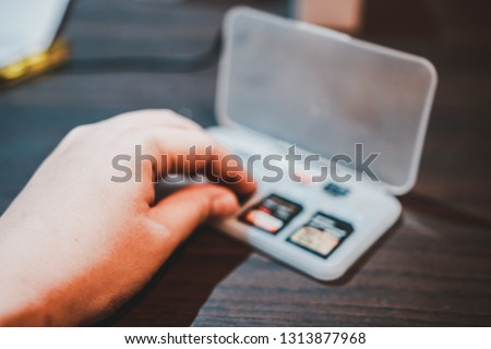 Hand picking SD card in a plastic storage box on the wooden table to be put in portable electronic devices like camera or camcorder #1313877968