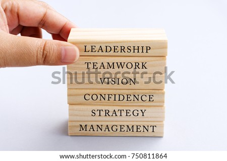 Hand Picking Wood Block with Word Leadership. Business Concept - Wood Top Block with Word: Leadership, Teamwork, Vision, Confidence, Strategy and Management.