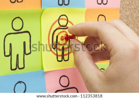 Hand pinning a sticky note in the center of a customer target on cork board