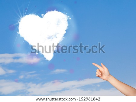 Hand pionting at white heart cloud on blue sky concept