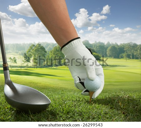 hand placing a tee with golf ball