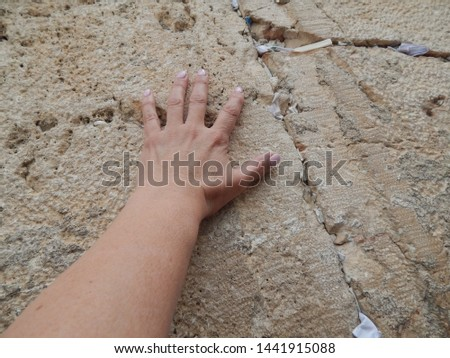 """Hand placing a wish. Western wall or """"Wailing wall"""" in Jerusalem with prayers written down and placed in the cracks.  #1441915088"""
