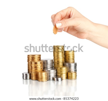 Hand placing coin on stack of coins