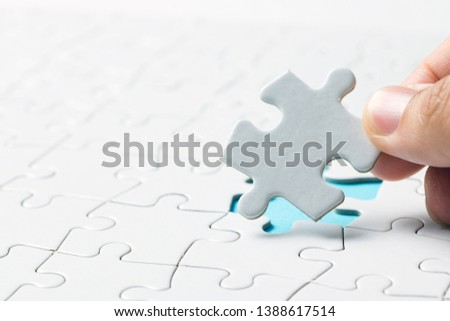Hand placing the last jigsaw puzzle piece or holding missing jigsaw puzzle piece down in to the place #1388617514