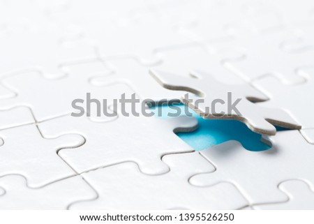 Hand placing the last jigsaw puzzle piece or holding missing jigsaw puzzle piece down in to the place #1395526250