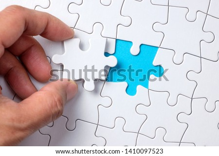 Hand placing the last jigsaw puzzle piece or holding missing jigsaw puzzle piece down in to the place #1410097523
