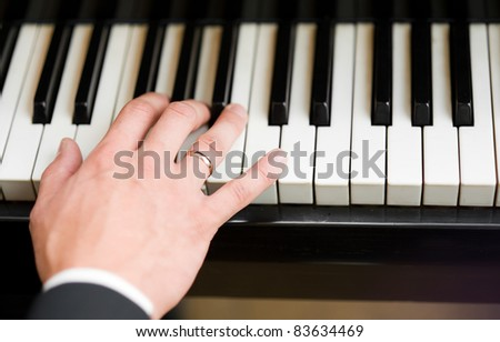 Hand playing music on the piano, hand and piano player