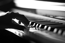 Hand playing on digital piano. Close-up. Small depth of field. Black and white.