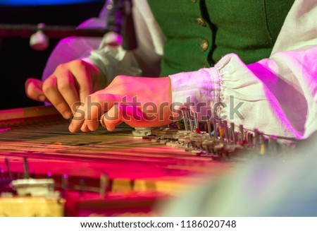 Hand playing on kokle a Latvian plucked string instrument belonging to the Baltic box zither family. #1186020748