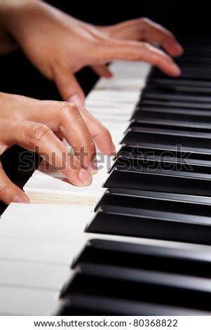 Hand playing on piano keys, using spot lighting