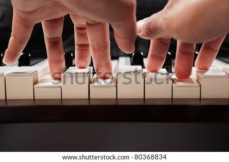 Hand playing piano taken from low angle point