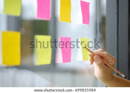 Hand point sticky note reminder on glass windows in business office. #699835984