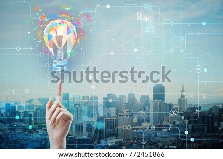 Hand pointing at abstract polygonal lamp on city background with circuit and copyspace. Power and idea concept. Double exposure