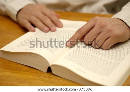 Hand pointing at page on a book. Shallow depth of field, focus on hand.