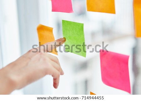 Hand pointing at sticky note with idea for business strategy #714944455