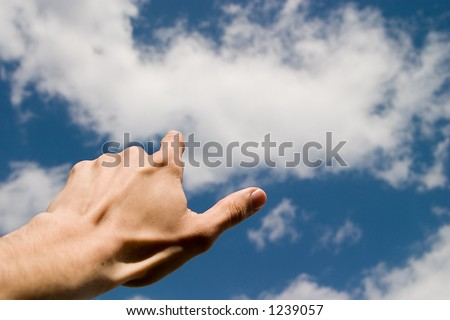 hand pointing the blue sky with white clouds